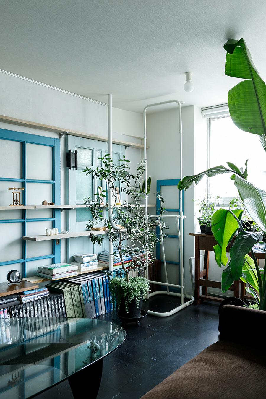 つきあたりの壁にたてかけた濃いブルーのはしごのような建具も同じく戦前の集合住宅で使われていたもの。手前はぶら下がり健康器。配管と合わせて白く塗装することで、空間になじませた。
