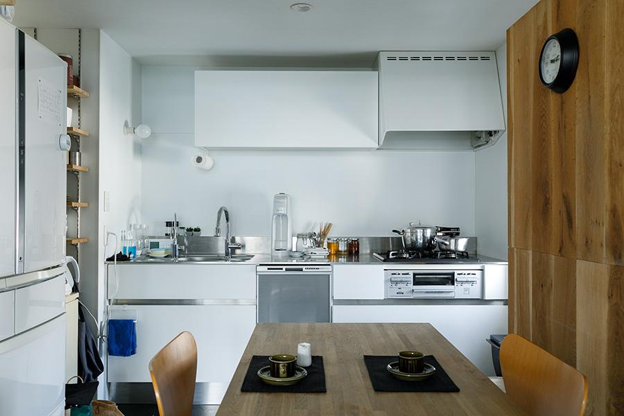 キッチンはシンプルに白で統一。右手の木の壁の奥は給湯器が隠れている。