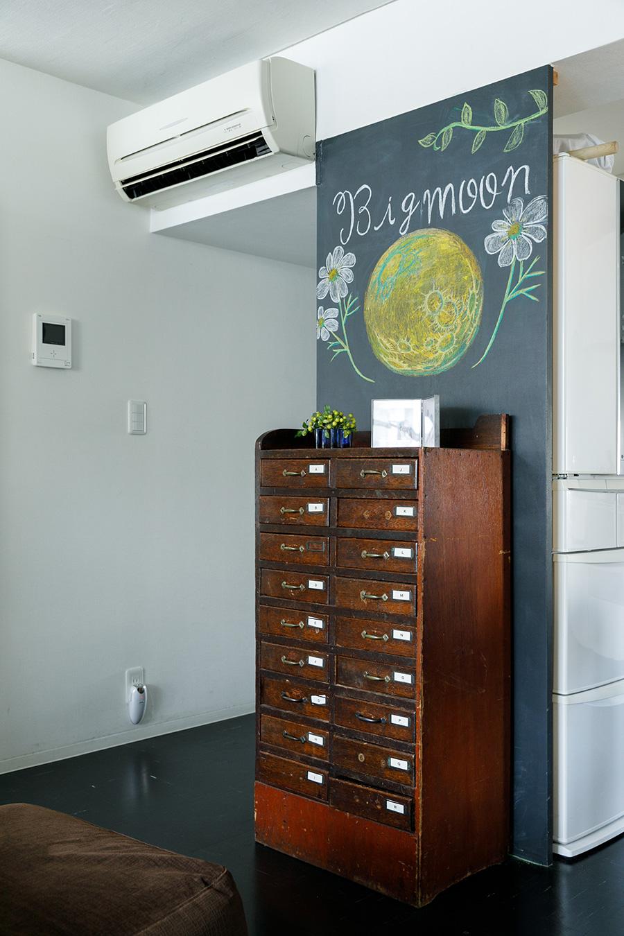 廊下の横の黒板は、キッチンの冷蔵庫を隠すために設けたもので、絵は次女が描いた。箪笥は捨てられていたものを譲り受けた。「把手のない引き出しもありますが、小分けになっているので便利です」。