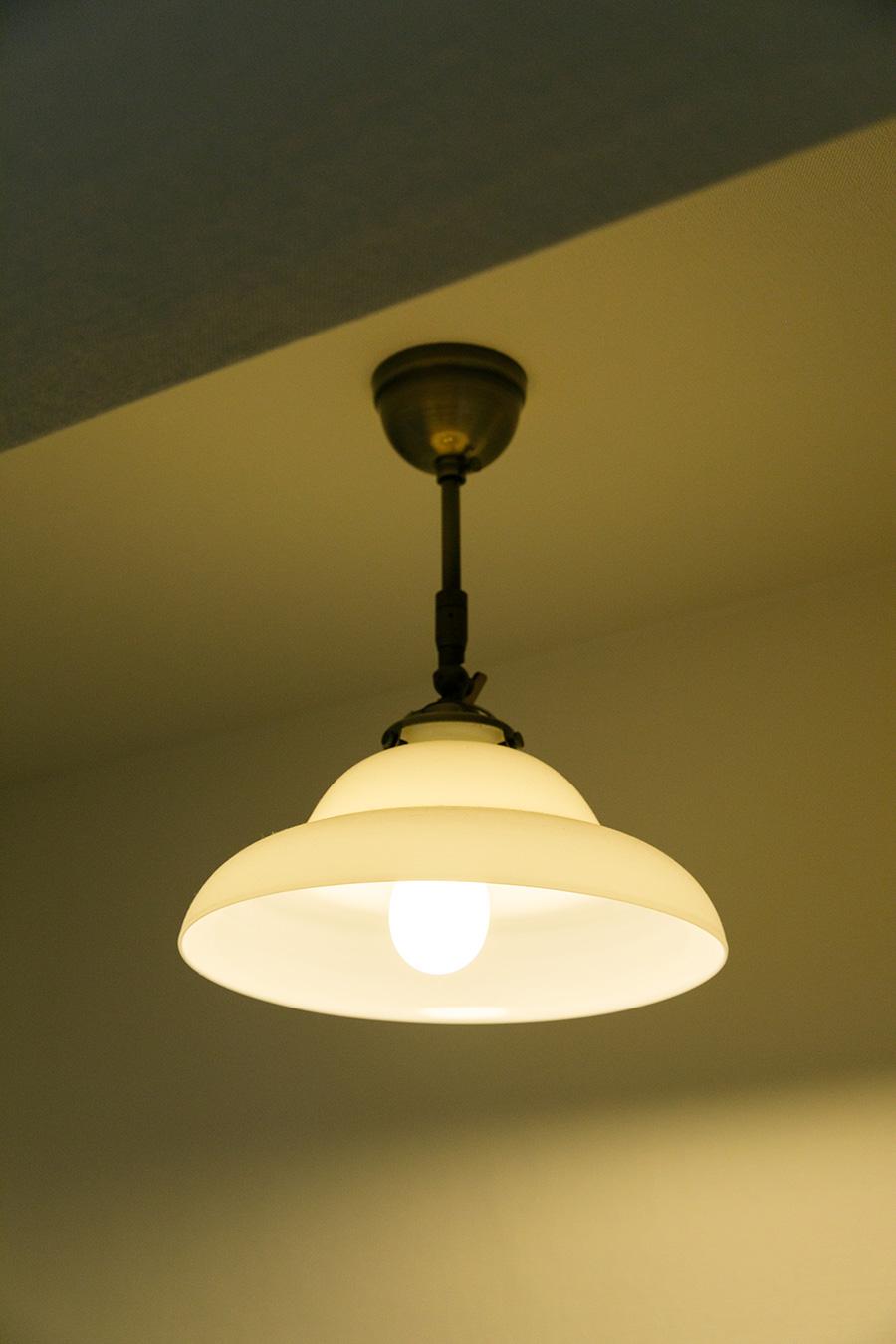 柔らかな光が魅力的な玄関のランプシェード。戦前の集合住宅で使われていたものを使っている。