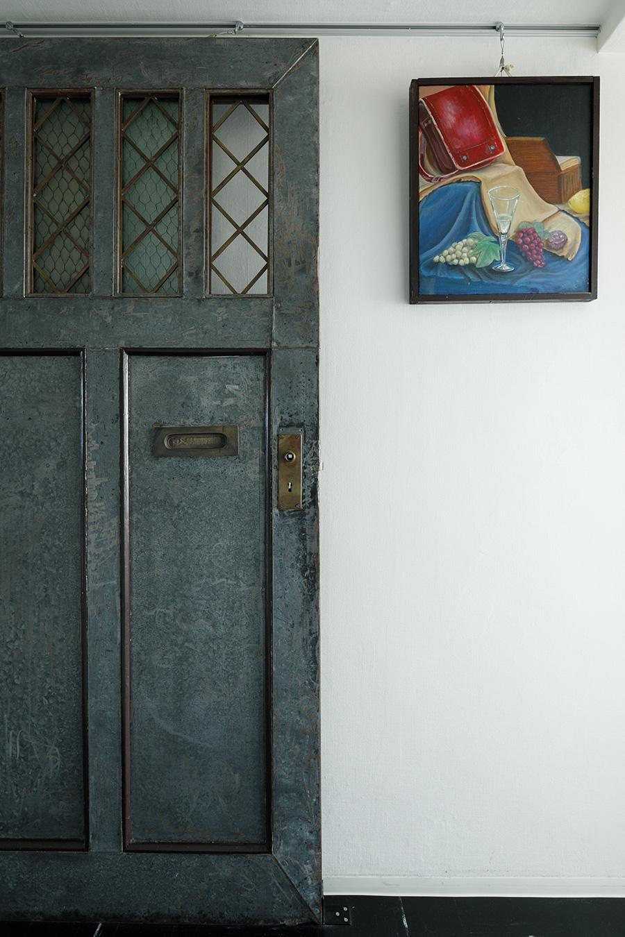 廊下に飾られた戦前の集合住宅の共同玄関の建具。ピクチャーレールを使って倒れないようにしている。