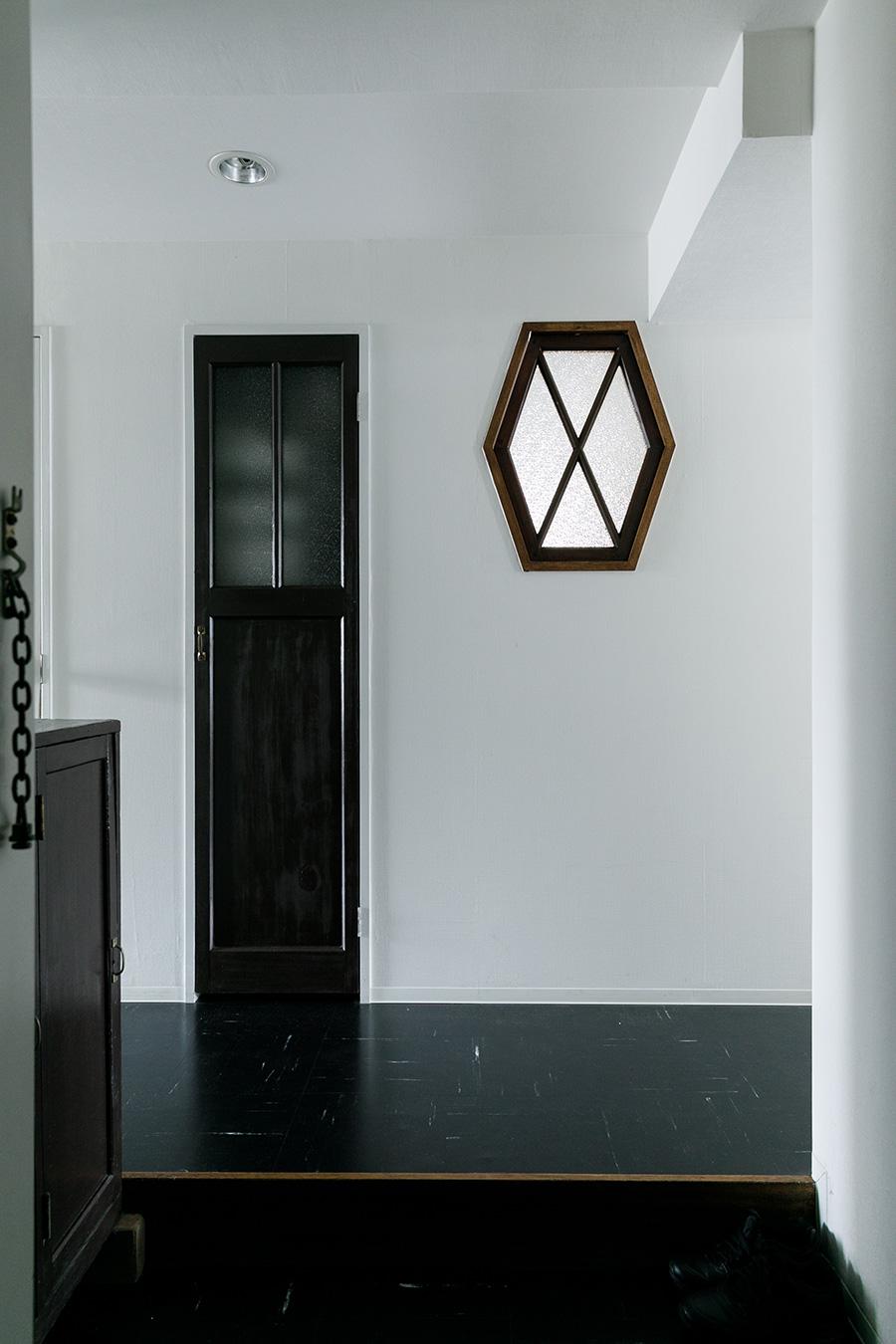 キッチンの六角窓を廊下側から見たところ。玄関を入ると、まず六角窓が目に飛び込んで来る。左側の細長い戸の奥は収納スペース。
