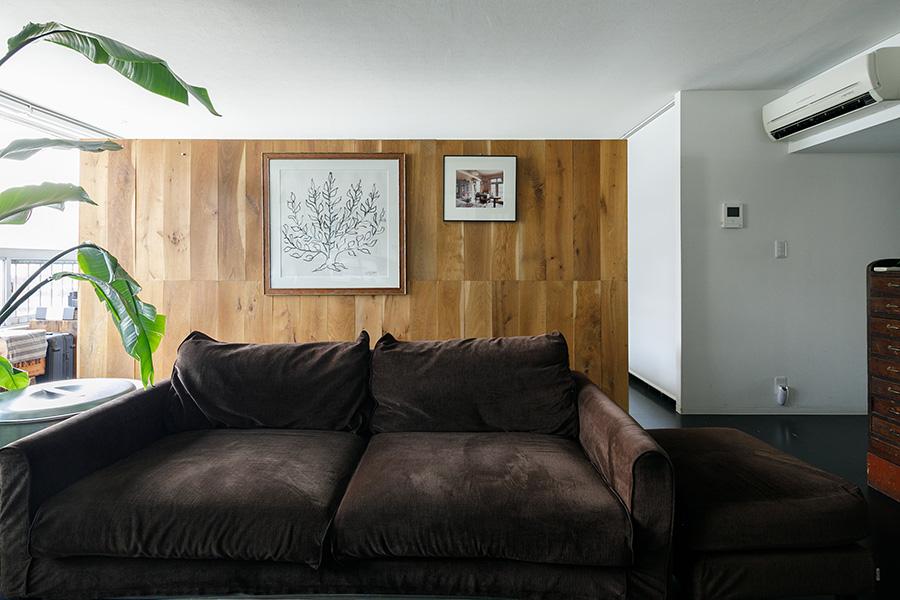 リビングのソファの背面に壁をたて、その向こう側が夫妻の寝室兼書斎スペースに。完全な間仕切りにしないことで開放感を味わえる。