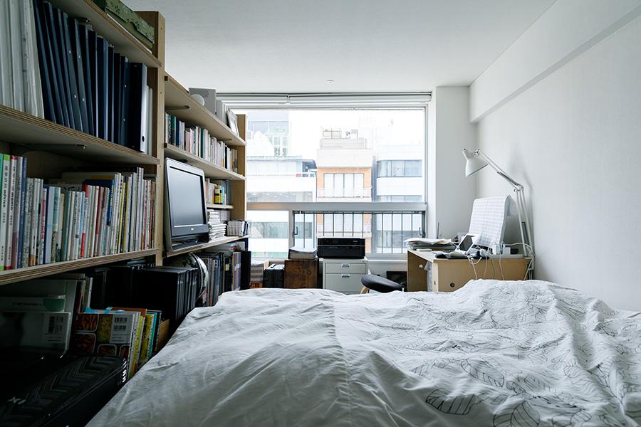 夫妻の寝室兼書斎。ベッドを挟んで写真の手前側にもデスクがある。壁の裏側は造り付けの書棚とし、夫妻それぞれの蔵書を収めた。