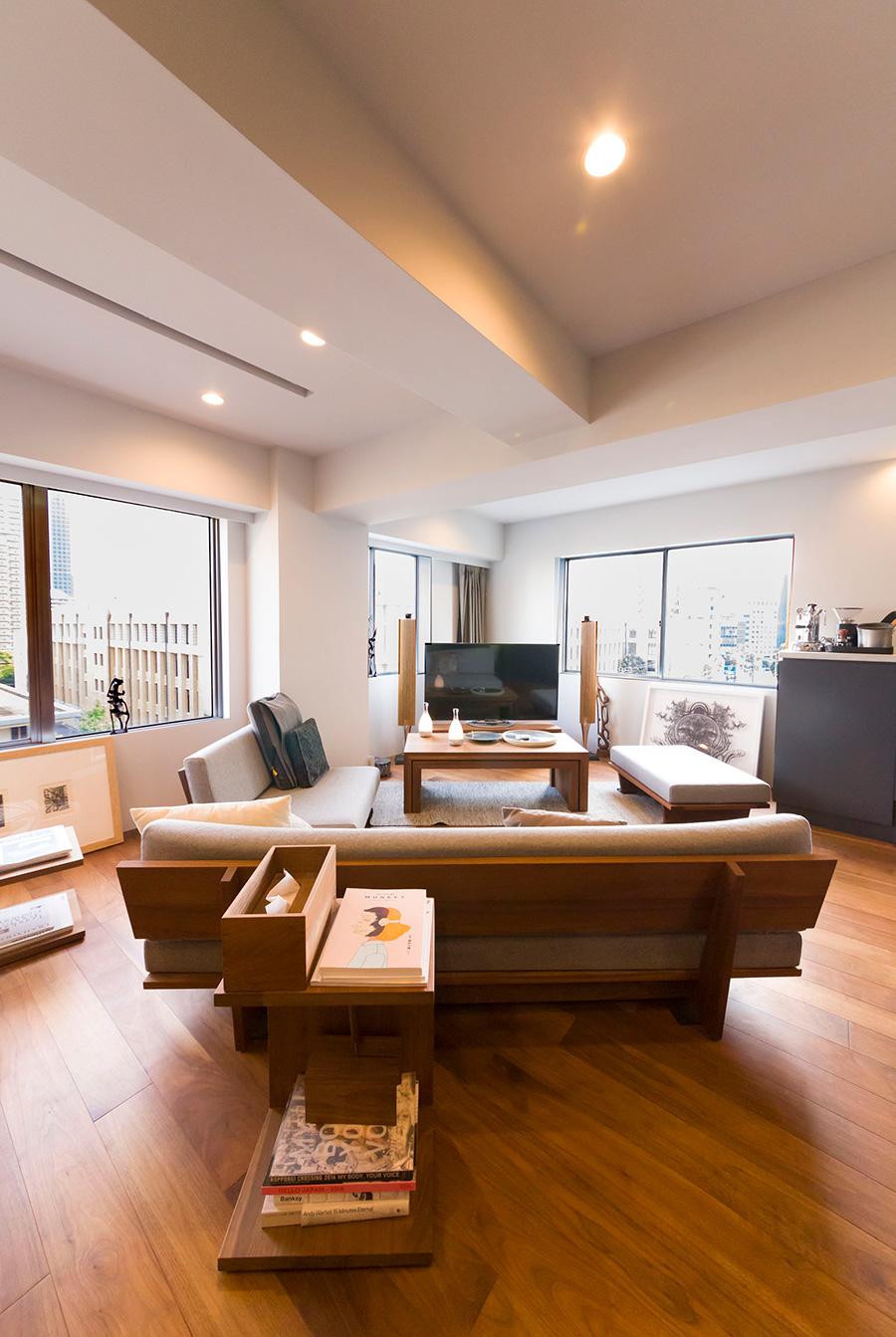 ウォールナットの背板が美しいソファは、大胆にリビングに対して斜めに設置。窓の外には東京タワーが見える。