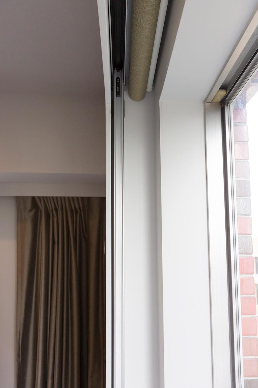 壁をふかして、間に電動カーテンを収納。「多少部屋が狭くなってもなるべくフラットに見えることを優先しました」