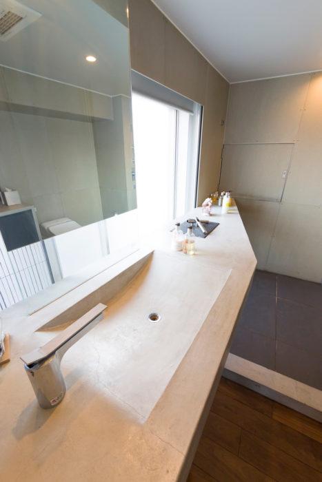 モルタルで造作した洗面ボウル。ガラスの一部を鏡にして、宙に浮いているようなイメージに。洗面台はガラス扉をはさんでキッチンまで一直線に繋がっている。