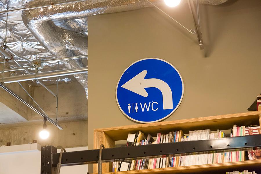 『オープン・エー』のオフィスのトイレの場所は、道路標識を利用したもので案内している。