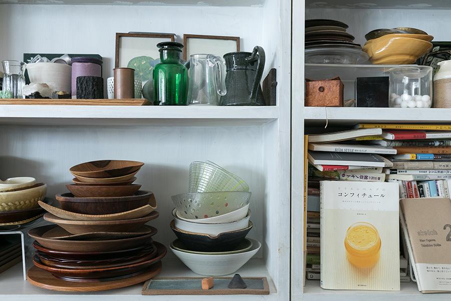 自作の木の棚には、小物や食器棚に入らない器、本などさまざまなものを飾りながら収納。