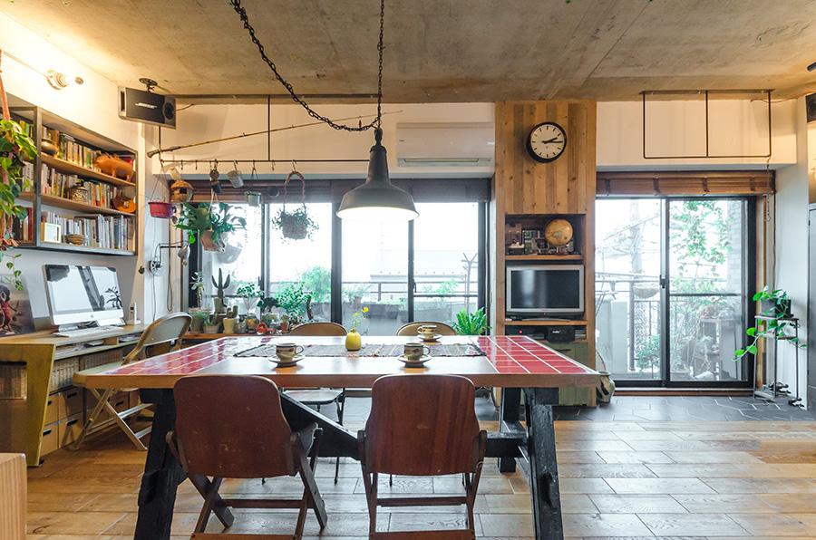 ヴィンテージ感のある床に、赤いタイルをあしらったダイニングテーブルがアクセントに。エアコンのホースが出ていた窓側の一角は、木で囲んで隠すとともにTVなどの棚に活用。