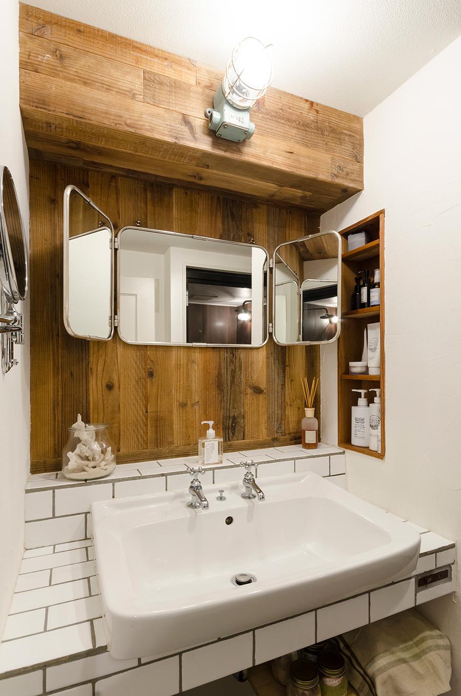 洗面は、白いタイルと木のナチュラルな風合いに、マリンランプがインダストリアル感をミックス。