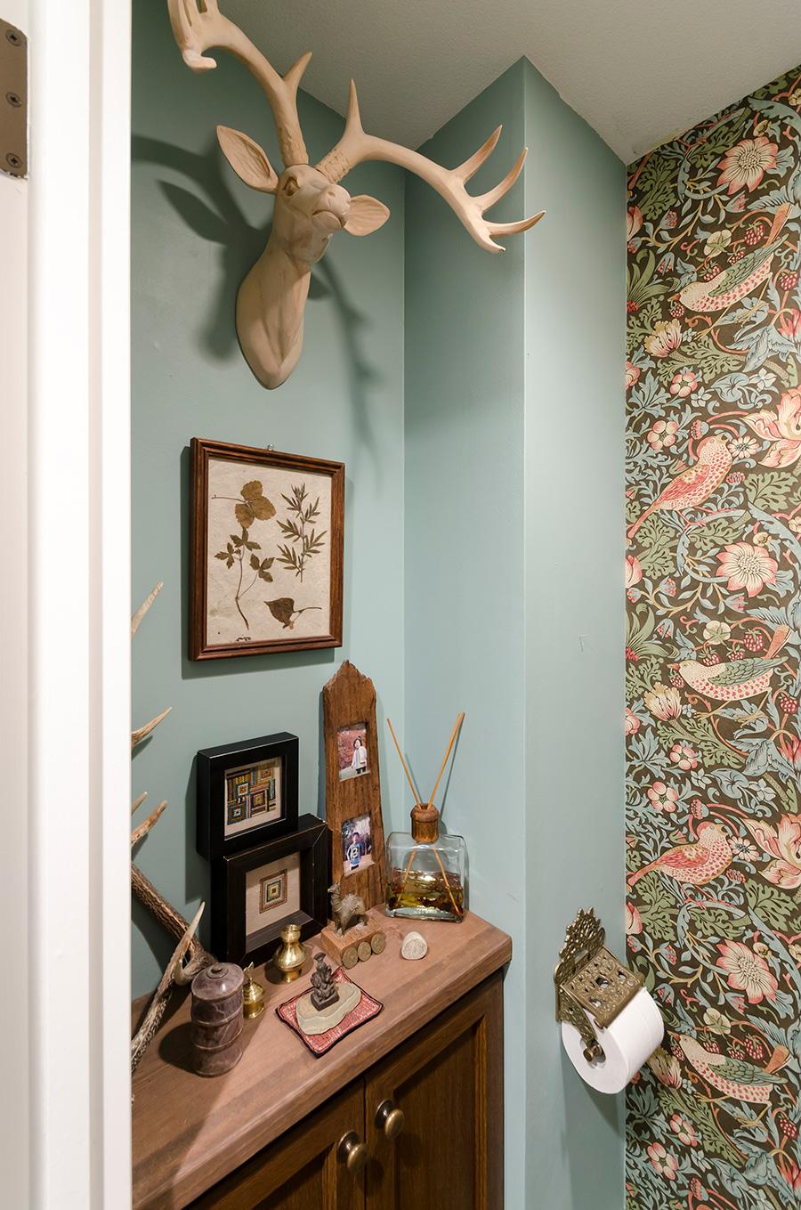 """ウイリアム・モリスの壁紙を貼ったトイレは、""""フォレストガーデン""""がテーマ。旅の思い出コーナーでもある。"""
