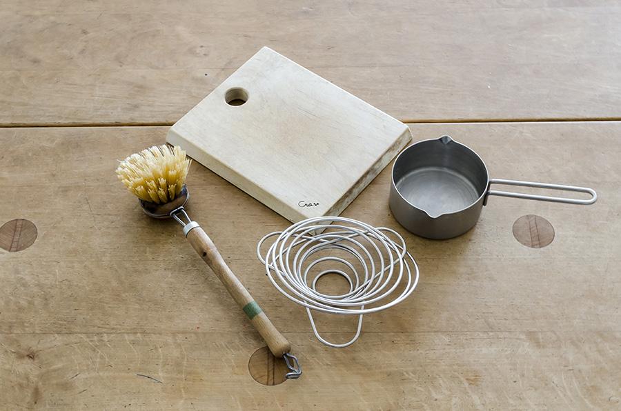 よく使うのでシンク前に吊るしている道具。アウトドア用コーヒーバネット、レデッカーの柄つきブラシなど。