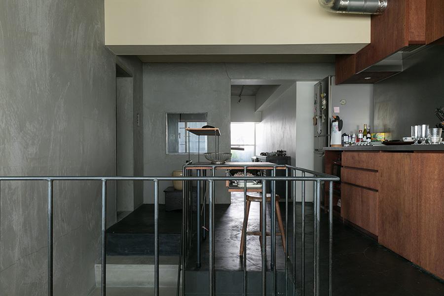 壁のモルタルのグレー、梁の白、床の黒、ラワン合板に着色した造作家具の茶色のバランスが美しい。アイアンの階段の手すりは特注。