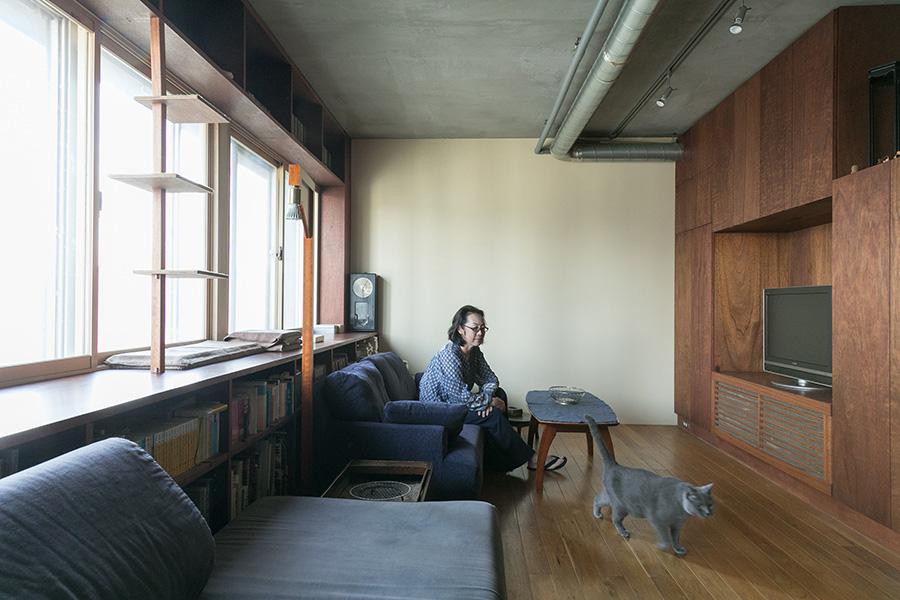 グレーの毛並みが美しいシャルトリューという品種のグリ。約50年前の建物とは思えないデザインの、大開口の窓が気持ちいい。窓際のキャットタワーはDIY。向かって右側には大容量の収納スペース。