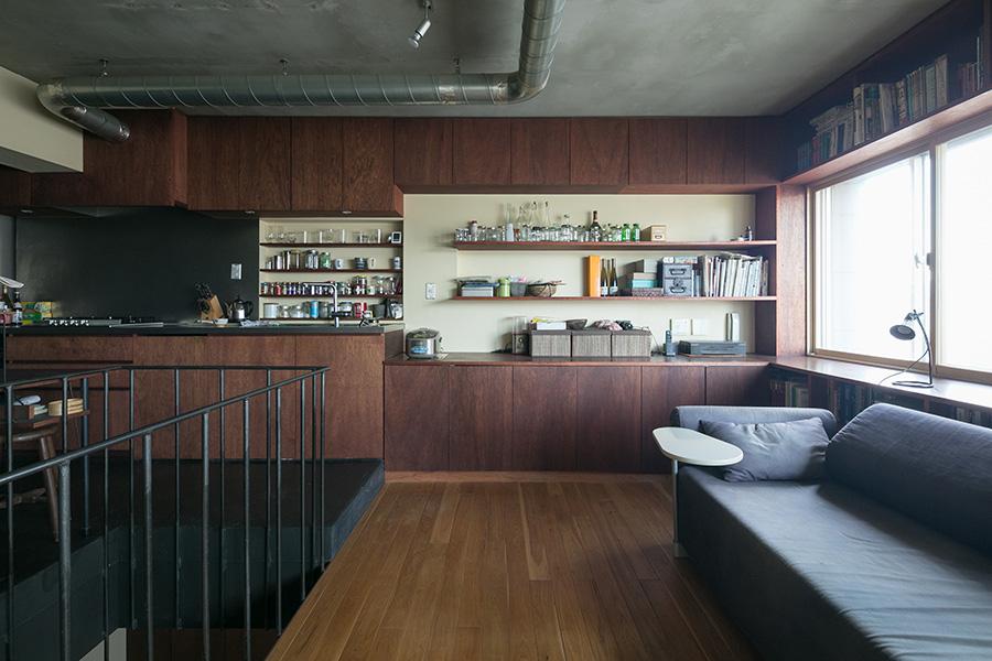 窓の上下に書棚。キッチンの床は黒のモルタル。「黒い床は、モルタルに炭を混ぜています。年に1度、撥水剤を塗っているので、シミなどが残りにくいようです」
