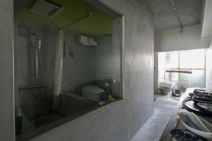 大きなガラスの向こうが浴室。ブロックを積んでモルタルで塗装した浴槽。お湯を張れば、温泉気分を楽しめる。