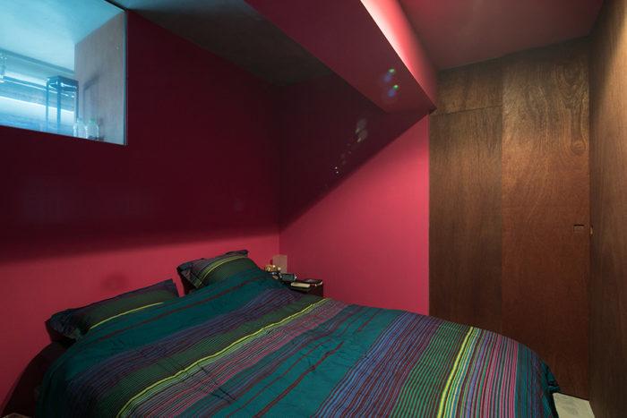寝室は大胆な壁色、バラガンピンクに。左側のガラス窓から光が入る。ラワン合板の引き戸の向こうは大容量のクローゼット。