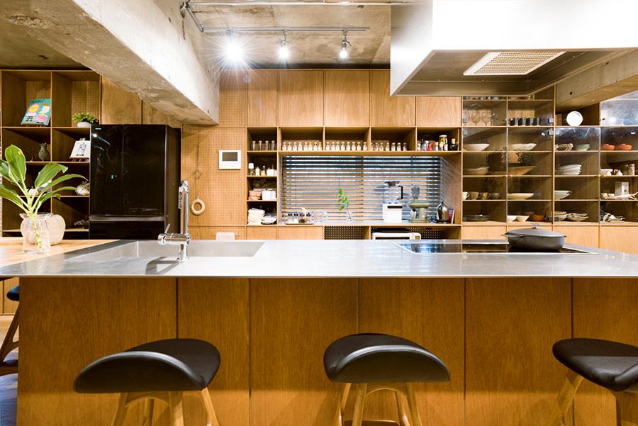 キッチンカウンター下のラインは、棚の縦ラインに揃えられている。棚板などは9ミリの厚さで金属のようなシャープさを表現。カウンターに合わせたスツールはエリック・バックのリプロダクト。