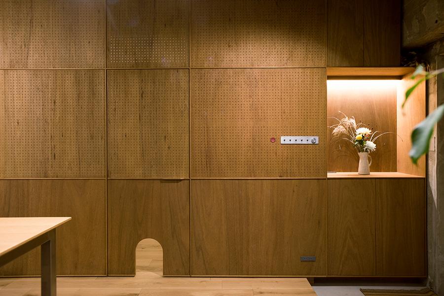 プライベートスペースを分けるラワンの板は、有孔ボードと直線のラインをアクセントに。愛猫のドアも設置。