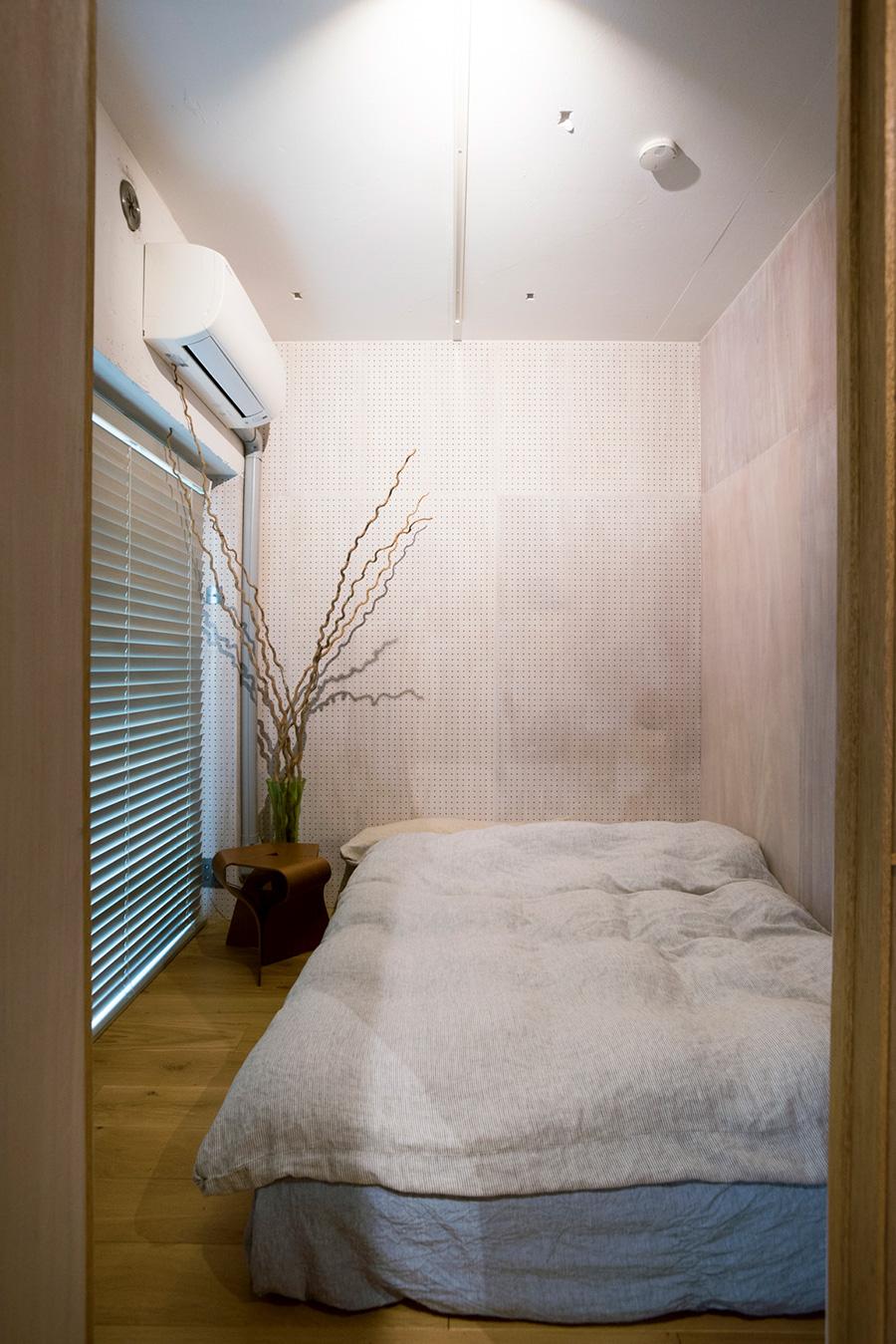 流木をオブジェに飾ったシンプルなベッドルーム。