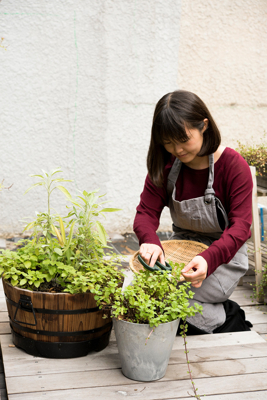 ウッドデッキを敷いたテラスでハーブを摘む桃子さん。デッキはすのこ状にして移動できるよう工夫した。