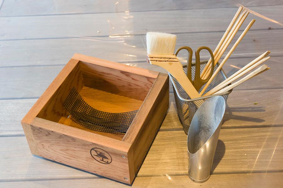 鉢底には水はけのためのスリットが開いているので、土が流れないよう鉢底ネットで覆う。スコップがあると土を入れやすい。割り箸は土を隙間なく押し込む時に使う。