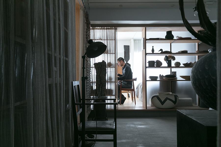 手前が吉田有志さんが集めた古道具や現代アートを飾るギャラリースペース。「うちにある自分が好きなものの多くは、gallery takamineで購入しています」。奥がリビングとベッドルームになっている。