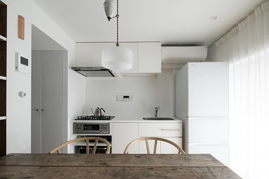 シンプルで必要十分なキッチン。手前のテーブルはフランス製のアンティーク。左奥の通路の先に浴室などのユーティリティがあり、そこからもギャラリーに出られるよう回廊式の動線を確保。