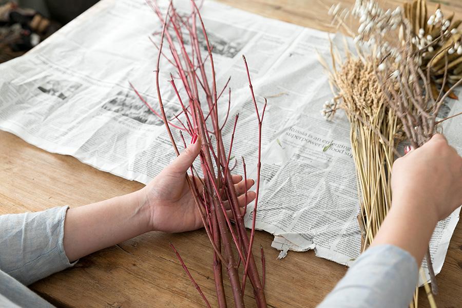 [1]飾った時に下になる枝ものを左手に取り、順に花材を乗せていく。