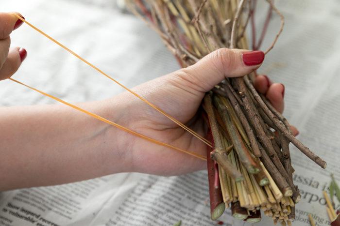 [5]輪ゴム2本をまとめ、一番太い枝に引っ掛け、グルグルと巻いていく。