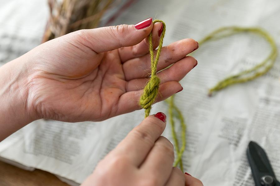 [7]麻ひもを2つに束ね、真ん中にスワッグを引っ掛けるための輪っかを作る。