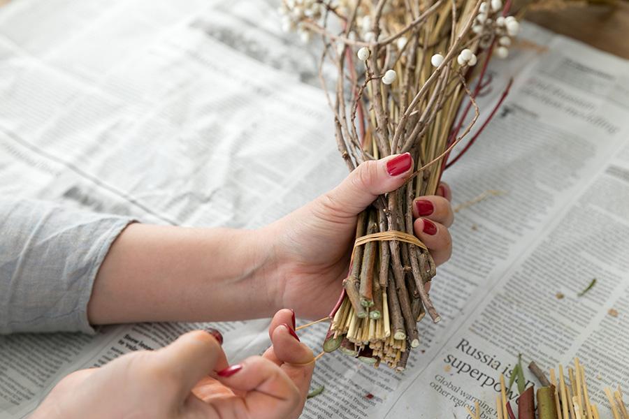 [6]花材が乾燥すると茎が痩せてくるので、緩まないようにしっかりと巻き、最後を枝に引っ掛けて留める。