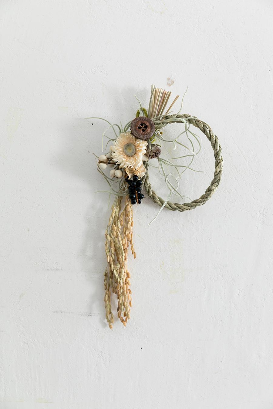 しめ縄と稲穂のお正月らしいリースに、ユーカリの実などの実ものや、ティランジアをあしらって。グルーガンを使って留めていく。