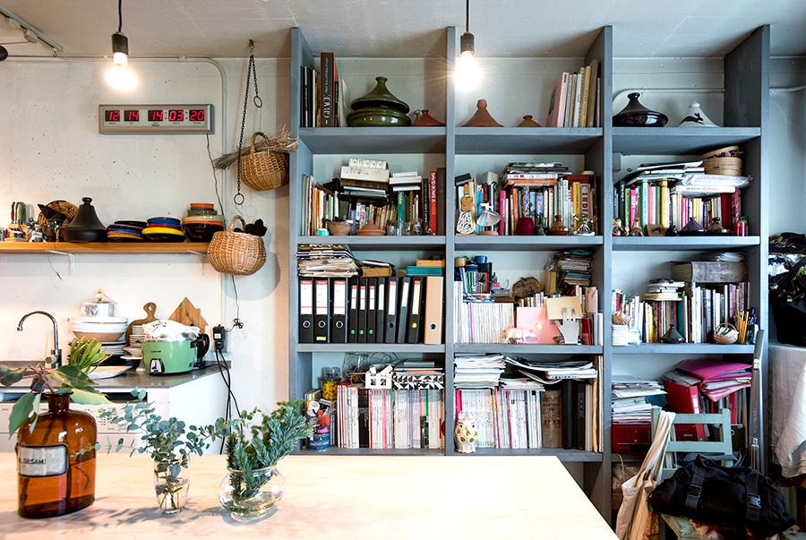 天井までの高さにこだわってオーダーした本棚。テーブルは料理教室のために、大きな天板をソーホースに載せて使用。