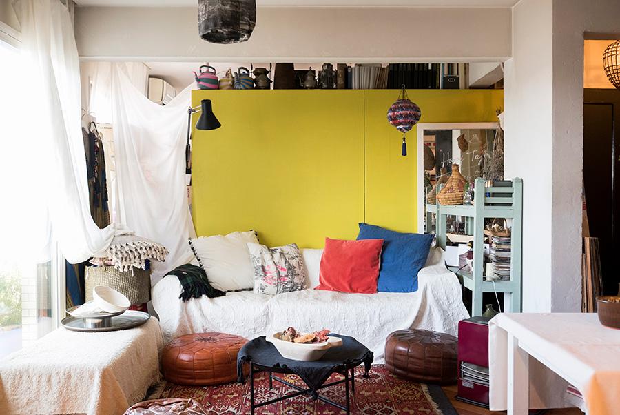ベッドルームとの仕切りは、収納を利用。モロッコのソファークッション・プフや、照明などがエスニックなムードを醸し出すリビング。