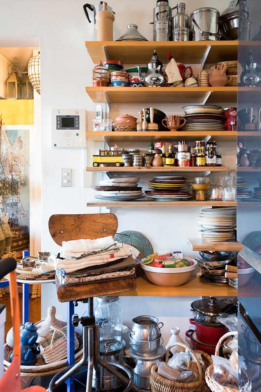 壁に可動式の棚を取り付けて収納に活用。あらゆる国籍のキッチンツールが並ぶ。