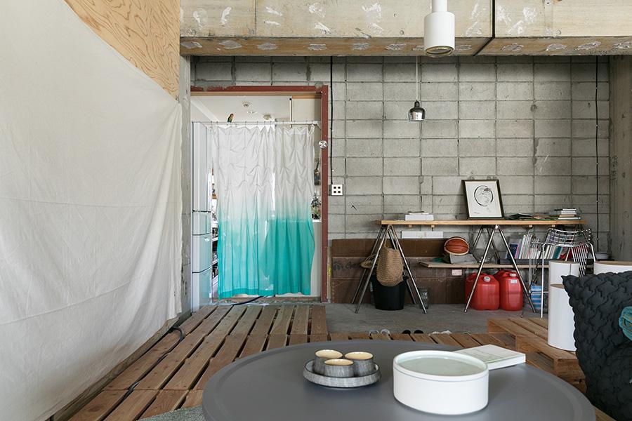 コンクリートの床に、必要な部分だけパレットを敷いている。パレットは、家でワークショップを行う時には積み上げてテーブルのように使うなど、臨機応変に使いまわせるのが強み。カーテンの向こうがキッチンとベッドルーム。