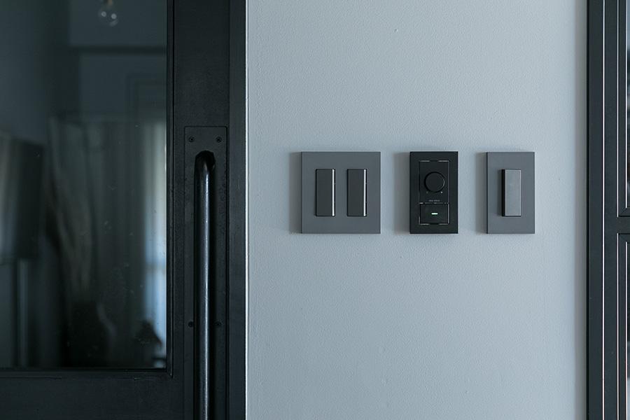 スクエアなデザインのグレーのスイッチプレート。扉の黒、壁の薄いグレーとの色のコンビネーションも美しい。