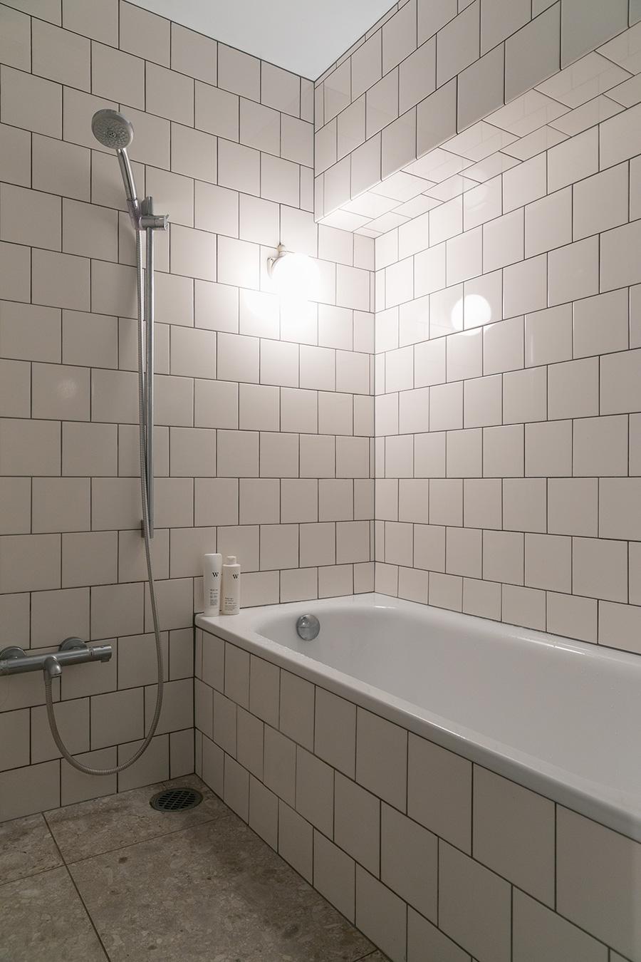 正方形のタイルと天然石の床がホテルライクなバスルーム。シャワーヘッドはグローエをチョイス。