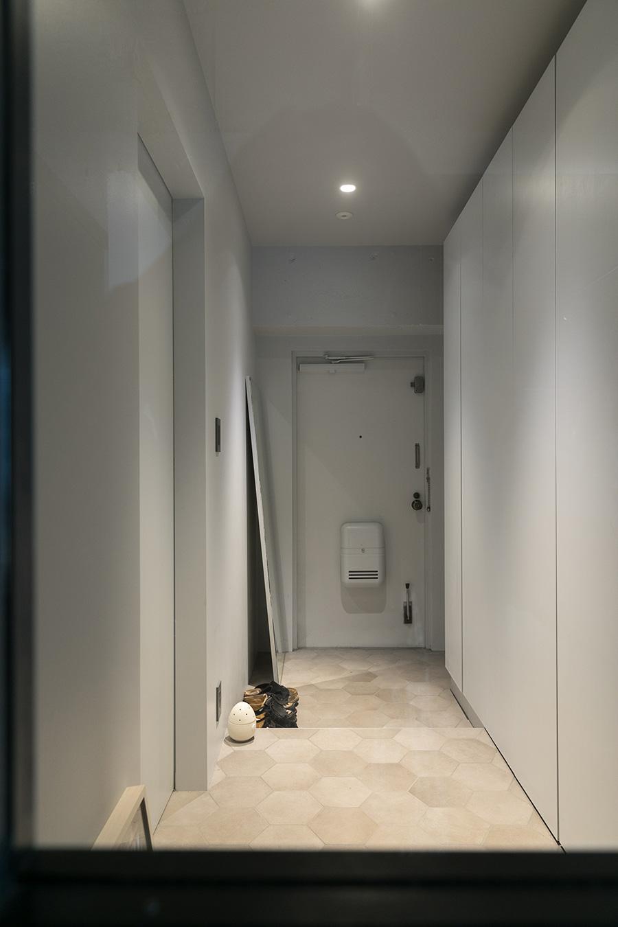 エントランスは六角形のタイルを使っている。リビングと廊下の間のドアには大きなガラスを入れて見通しを確保。