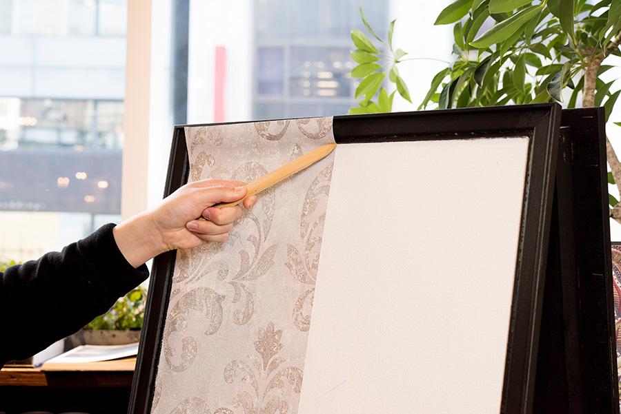 上下の端っこの処理を行う。竹ベラを使って、壁紙を奥の方まで、右から左へ押し込んでいく。
