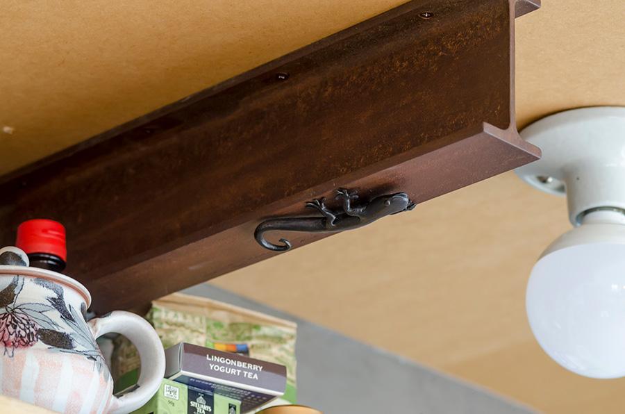 知人にオーダーした鉄の支柱が棚板を支える。家を守るヤモリもオーダー。
