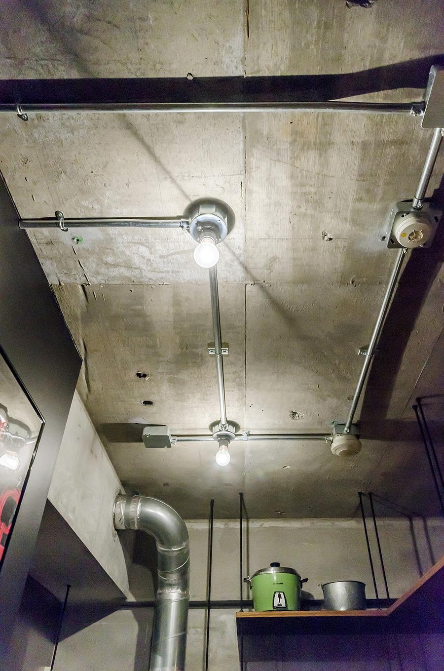 打ちっ放しの天井を走る配線パイプや排気のダクト。