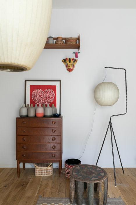 チェストの上に、Heath Ceramicsの一輪挿しと、Alexander Girardのファブリックの額装を飾っている。鳥かごスタンドに掛けているのはGeorge Nelsonのバブルランプ。足元にはアフリカのスツール。