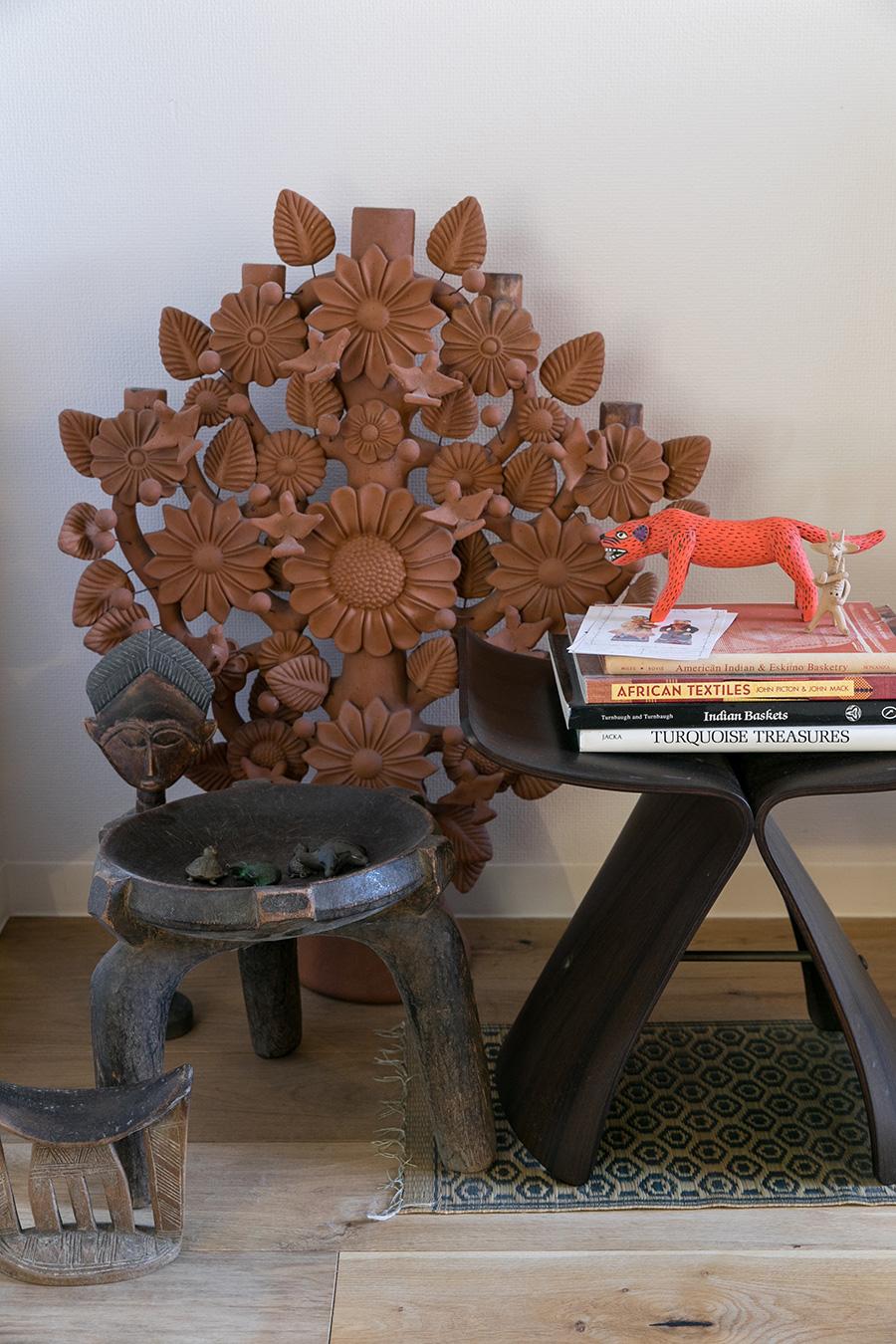 奥はメキシコの伝統工芸品Tree of Life(生命の樹)。「一家に一台はあるものと聞いています。彩色していない素焼きのものは珍しいと思います」。柳宗理のバタフライスツールと、アフリカの民藝のスツールや枕を一緒に飾る。