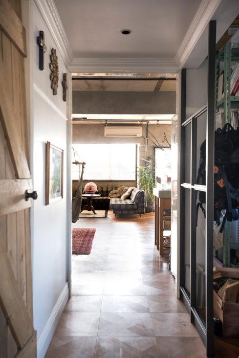 あえて天井を低くした廊下をくぐると、その向こうにLDKが。白い塗装にモールディングが、違う世界観を出している。