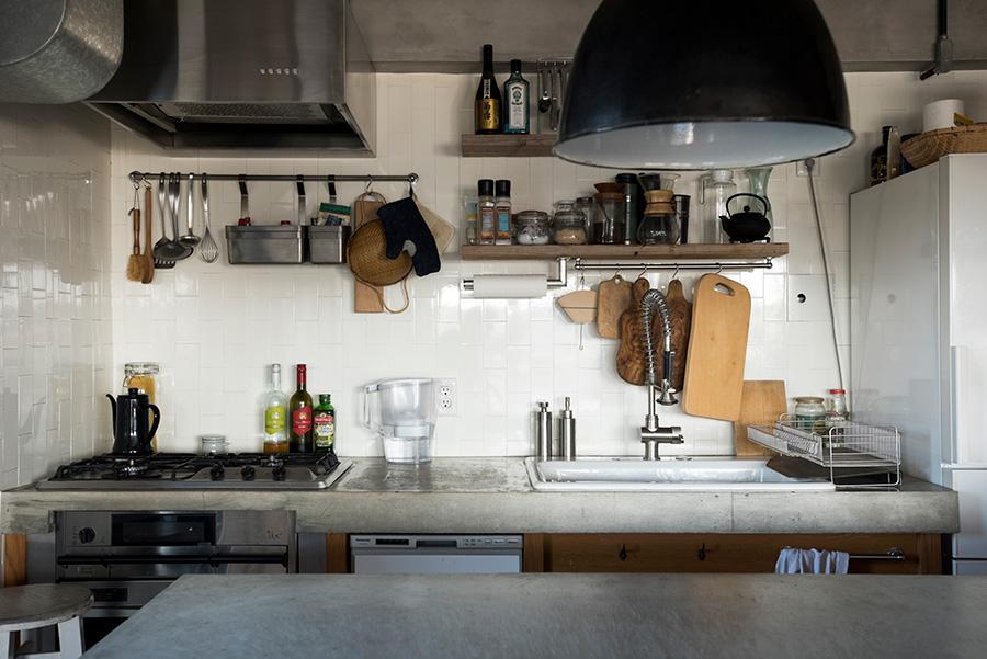 モルタルの天板と木を組み合わせたキッチン。キッチン台とアイランドの間の幅も考え抜いた。