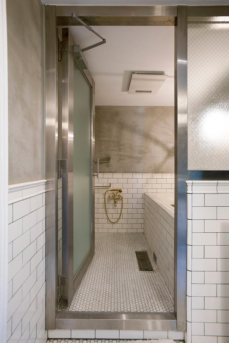 サブウェイタイルとモルタルの組み合わせがかっこいいバスルーム。ステンレスの枠と曇りガラスでドアを発注。