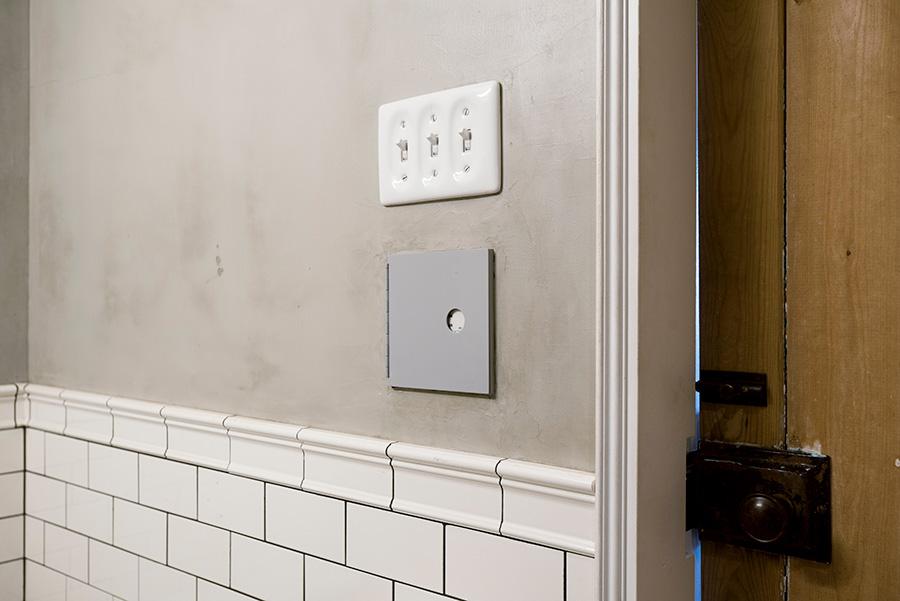 スイッチは壁に埋め込み、特注の蓋で隠した。パネルはすべて陶器製に。